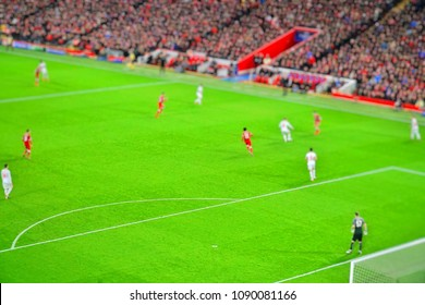Blurred background of football players playing and soccer fans in match day on beautiful green field with sport light at the stadium. Sports,Athlete,People Concept.Anfield,Mercyside,Liverpool,UK.