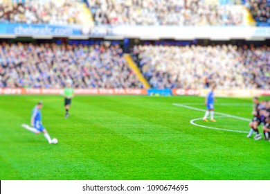 Blurred background of football players playing and soccer fans in match day on beautiful green field with sport light at the stadium.Stamford Bridge.Chelsea.London.
