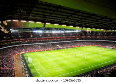 Blurred background of football players playing and soccer fans in match day on beautiful green field with sport light at the stadium.Sports,Athlete,People Concept.Arsenal,Emirates Stadium.