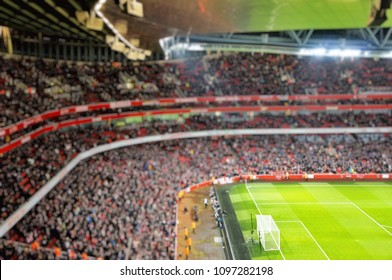 Blurred background of football players playing and soccer fans in match day on beautiful green field with sport light at the stadium.Sports,Athlete,People Concept.Emirates Stadium,Arsenal.