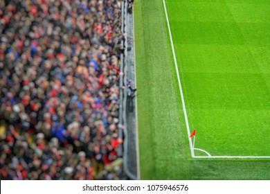 Blurred background of football stadium and soccer fans in match day on beautiful green field with sport light at the stadium.Sports,Athlete,People Concept.Anfield,Mercyside,Liverpool,UK.