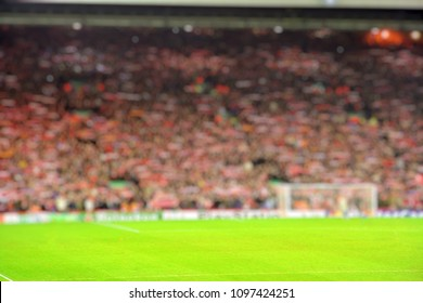 Blurred background of football stadium and soccer fans in match day on beautiful green field with sport light at the stadium.Sports,Athlete,People Concept.Anfield,Liverpool