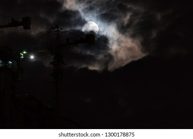 Blurred background of full moon in the cloudy night with tower crane.