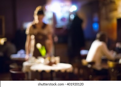 Blurred background, girl waitress in a cafe. The interior of the cafe in the evening. The waiter cleared the table.