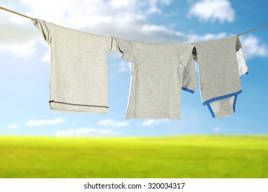 blurred background of grass and sky with hanging clothes