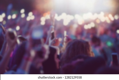 Blurred background with group of music hands waving with mobile phones lights on big concert.Musical festival crowd out of focus.Bokeh back ground with event audience on dance floor