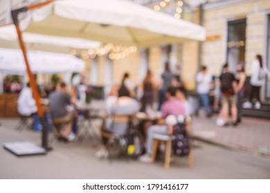 Blurred background with group of peolple sitting at the cafe veranda outside.