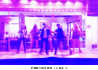 Blurred background of a group of people dancing in an indoor party