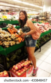 Blurred background of a happy lady in a grocery shop