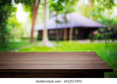 Blurred background of home garden picnic and wooden table free space for product display
