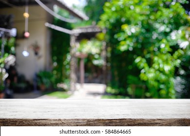 Blurred background of home garden and wooden table free space for product display.