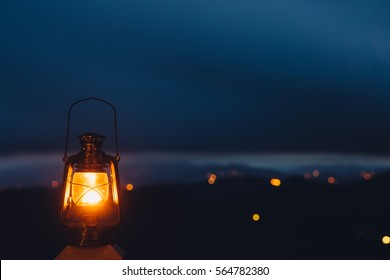 Blurred background image of a glowing lantern against dark night time mountains with lights