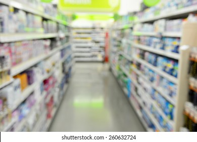 Blurred background image of shelves of items for sale inside of a retail store.