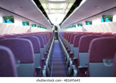 Blurred background of an interior of an aeroplane, showing aisle, economy class seats, monitor, ceiling, ceiling light, overhead bin compartments, cockpit door, cockpit room.