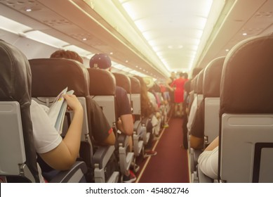 Blurred background of interior aircraft , flight attendant helping passenger to put luggage cabin compartment.