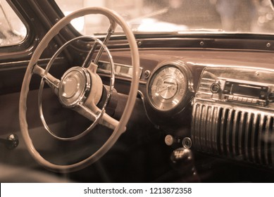 Blurred background - interior of a vintage car, styled as an old sepia photo with dust and scratches