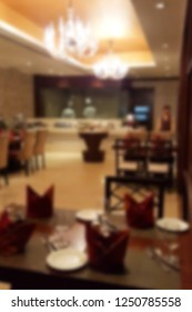 Blurred background of luxury restaurant with chef at open kitchen and waiter in scene.