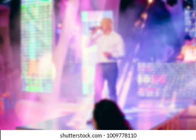 Blurred for background MC on club stage during open air night party. Night party on beach open air festival.