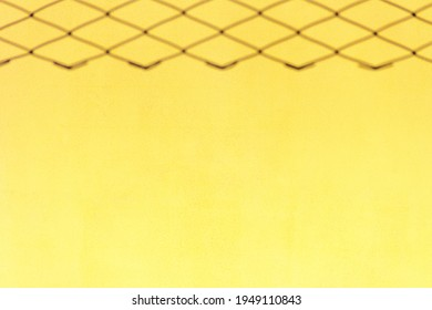 Blurred background of metal chain fence out of focus on yellow background. Located on top. With place for text.