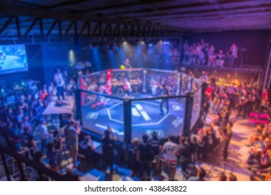 blurred background of mma fight octagon stage with many audience