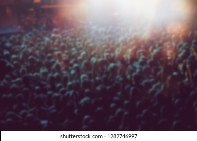 Blurred background of music festival crowd partying on dancefloor in nightclub.Big group of people rave to famous dj in the club.Out of focus blur with concert audience in green stage lights