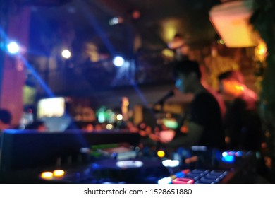 Blurred background of musician brand is playing music in the local bar or night club, too many people enjoyed. Photo contain some noise and blurred detail due to low light environment.