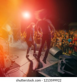 blurred background, musicians on stage during a performance in front of a crowd. Rock concert at night on a city street.