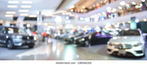 Blurred background of new cars displayed in luxury showroom with light bokeh in motor show event, panorama