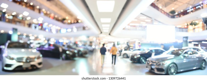 Blurred background of new cars displayed in luxury showroom with light bokeh, motor show event, panorama