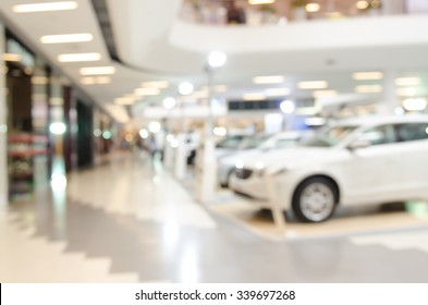 Blurred background of new cars displayed in showroom.