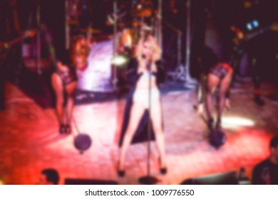 Blurred for background night club. Artist performs songs and club show from stage during concert at nightclub. Artist on club stage during night party.