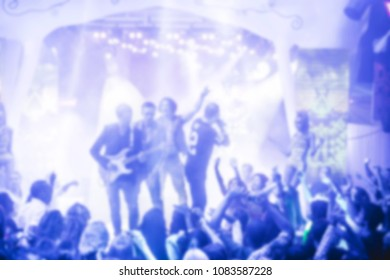 blurred for background night club. Artist performs clud show from stage during concert at nightclub with lights show. Artist on club stage during night party