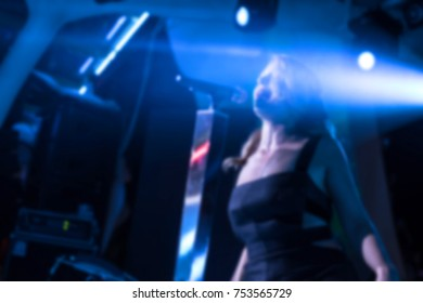 Blurred for background. night club party. Artist performs songs and club show from stage during concert at nightclub. Artist on club stage during night party.