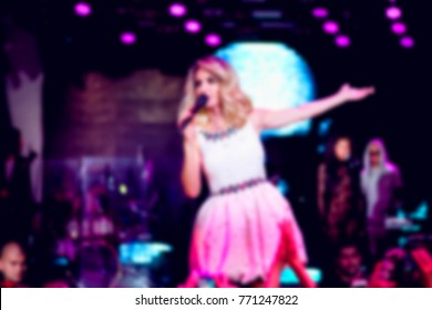 Blurred for background. night club party. Artist performs songs from stage during concert at nightclub. Artist on club stage during night party.