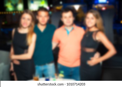 Blurred for background night club. People smiling and posing on cam during concert in night club party. Man and woman have fun at club. Boy and girl at night club party