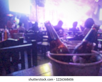 Blurred background night scene of alcohol bottle in ice bucket at the pub and restaurant with the beautiful violet color light