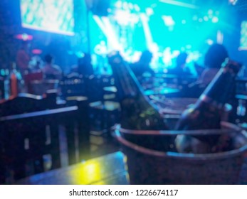Blurred background night scene of alcohol bottle in ice bucket at the pub and restaurant with the beautiful color light