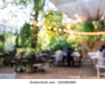 Blurred background of outdoor restaurant with abstract bokeh light.