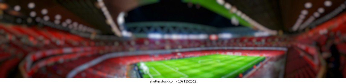 Blurred background of Panorama view of football stadium and soccer fans in match day on beautiful green field with sport light at the stadium.Sports,Athlete,People ,Banner Concept.Emirates Stadium.