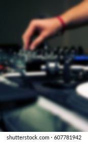 Blurred background of party dj audio equipment in night club.Disc jockey play & mix music on a party in the club.Out of focus dj turntable & audio mixer back ground for parties in nightclub