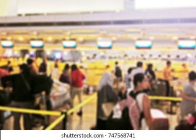 Blurred background of passengers falling in line in the check in area of the airport