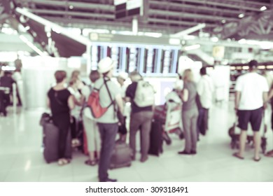 blurred background : passengers waiting and looking at time schedule at the airport terminal -  blur background concept