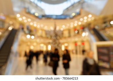 Blurred Background Pedestrians in Christmassy Illuminated Shopping Centre