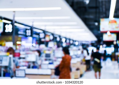 Blurred Background Of People In Department Store. Crowd Of Anonymous People Walking In Shopping Mall.
