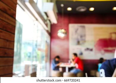 Blurred background of people inside fast food restaurant.