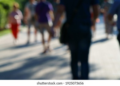 Blurred background. People walk on the city alley.