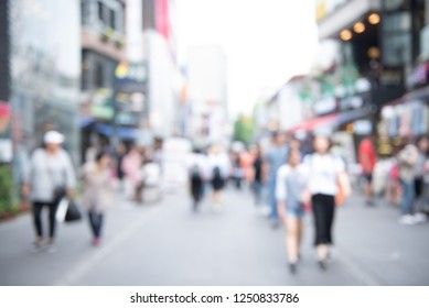 Blurred background, people walking at outdoor street market, business area in the city. Crowd street in Korea. Summer Holiday Shopping