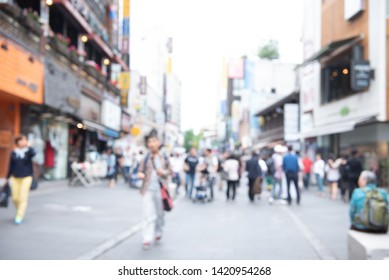 Blurred background, people walking, shopping at outdoor shady walking street market in the city. Summer Holiday shopping in Korea