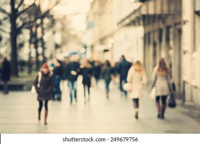Blurred background. Blurred people walking through a city street. Vintage toned photo.