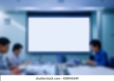 Blurred background of people working together as a team in an office with a blank board in the middle which allows you to put on any text, e.g., job advertising, promoting team building, etc.